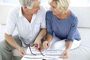 Ehepaar sitzt auf der Couch und studiert die Leitlinien